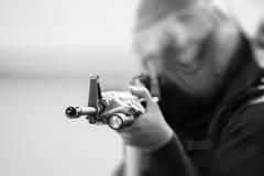 Тактическая полиция в тактической шестерне направляет винтовку в черно-белом к Стоковые Изображения