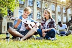 Талантливое молодые люди играя гитару и усмехаться стоковое изображение rf