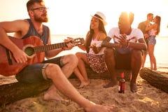 Талантливый гитарист играя гитару для друзей на пляже стоковая фотография rf