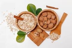 Там с грецкими орехами и свернутые овсы в деревянных плитах с ручками Sinnamon, деревянной поддержкой, ложкой, зеленым цветом вых Стоковое Фото