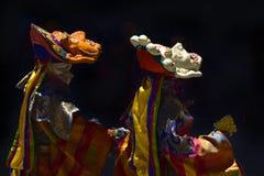 Танец буддийских ламов в масках: 2 монаха выполняют старый тибетский ритуал, маски одеты на голове и лицевой Стоковые Фото
