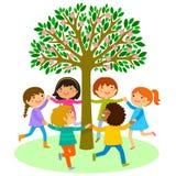 Танец детей вокруг дерева Стоковое Фото