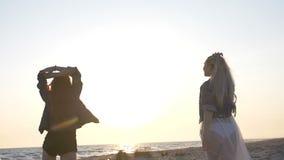 Танец на пляже 2 молодых сексуальных женщин одетых в стиле boho в свете захода солнца над морем акции видеоматериалы