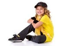 Танец: Танцор хмеля маленькой девочки тазобедренный при улыбка сидя на земле стоковые изображения rf