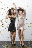 Танцевать 2 красивый женщин покрытый с confetti золота Стоковое Фото
