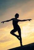 танцевать над йогой женщины захода солнца силуэта Стоковое фото RF
