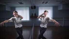 Танцор в белой рубашке и джинсах показывая современный breakdancing в классе с зеркалами и barre балета Молодой студент сток-видео
