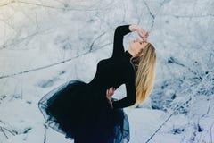 Танцор в черном платье в лесе снега стоковое фото