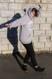 Танцуя moving девушка с расширенными оружиями в серой ткани против g стоковое фото
