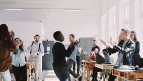 Танцы бизнесмена КРАСНОЙ ЭПОПЕИ счастливые молодые черные с confetti, празднуя успех с командой на замедленном движении партии оф сток-видео