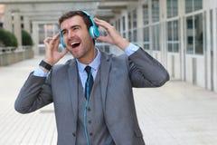 Танцы бизнесмена пока слушающ к музыке в размерах офиса Стоковое фото RF