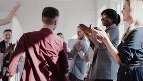 Танцы бизнесмена счастливой потехи молодые с многонациональной командой бизнесменов на ЭПОПЕЕ замедленного движения партии офиса  акции видеоматериалы