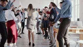 Танцы бизнес-леди босса счастливой потехи красивые молодые белокурые с многонациональной командой на ЭПОПЕЕ замедленного движения видеоматериал