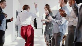 Танцы бизнес-леди руководителя счастливой потехи молодые кавказские с многонациональной командой на ЭПОПЕЕ замедленного движения  видеоматериал