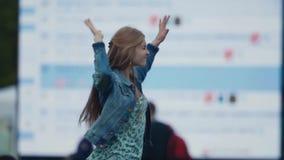 Танцы девушки замедленного движения молодые радостные перед большим экраном на музыкальном фестивале акции видеоматериалы