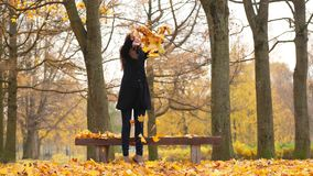 Танцы женщины, бросая в кленовые листы воздуха яркие видеоматериал