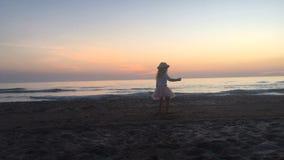 Танцы маленькой девочки на пляже на заходе солнца сток-видео