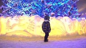 Танцы мальчика перед рождественской елкой внешней xmas Милый мальчик имея потеху outdoors в городе рождества мальчик имея сток-видео