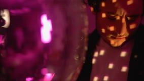 Танцы молодого человека около шарика диско, ослабляя на партии ночного клуба, беспечальная жизнь сток-видео