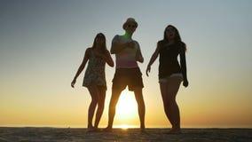 Танцы молодого человека на пляже с 2 женщинами на восходе солнца видеоматериал