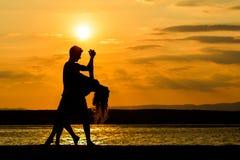 Танцы пар морем на заходе солнца Стоковое фото RF