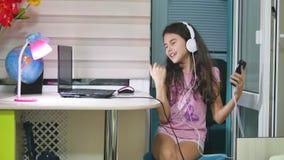 Танцы подростка девушки и петь в наушниках музыки школьница слушает к музыке онлайн и танцует внутри помещения и поет акции видеоматериалы