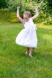 Танцы ребенка в траве Стоковые Изображения