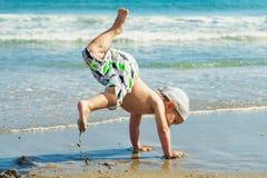 Танцы ребенка на пляже Стоковые Фото
