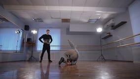 Танцы Breakdancer на танцплощадке и выполняют трудные эффектные выступления Молодой человек наблюдая как его танцы и взятия друга сток-видео