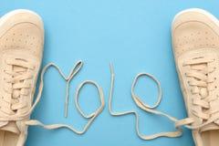 Тапки женщин со шнурками в тексте аббревиатуры yolo стоковая фотография