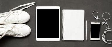 Тапки на черной предпосылке с телефоном, наушники стильного вскользь знамени белые, таблетка, книга экземпляра Стоковые Изображения