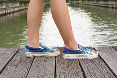 Тапки холста на ногах на деревянном мосте Стоковые Фотографии RF