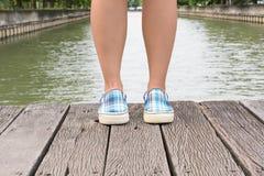 Тапки холста на ногах на деревянном мосте Стоковое Изображение RF