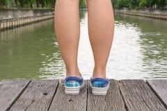 Тапки холста на ногах на деревянном мосте Стоковое фото RF