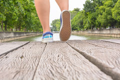 Тапки холста на ногах на деревянном мосте Стоковые Фото
