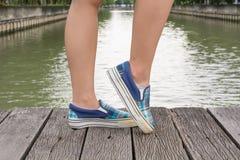 Тапки холста на ногах на деревянном мосте Стоковые Изображения