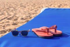 Тапочки и солнечные очки дальше sunbed на пляже Стоковая Фотография