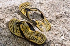 Тапочки Yelloe резиновые на пляже песка Стоковые Изображения RF
