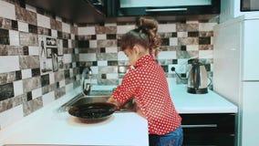 Тарелки маленькой девочки моя в кухне сток-видео