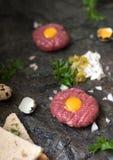 Тартар из говядины с замаринованным огурцом и свежими луками на темной мраморной предпосылке стоковое фото rf