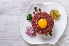 Тартар из говядины с концом яичка вверх на таблице Взгляд сверху стоковые фото
