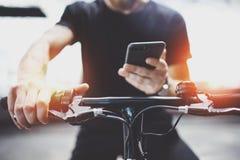 Татуированный человек хипстера в удержании рук смартфона и использовании приложения карт перед ехать электрическим скутером в гор стоковое изображение