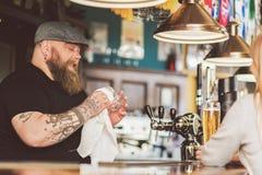 Татуированный человек концентрируя на работе пока стоящ в пабе Стоковое Изображение RF