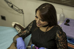 Татуировка деятельности художника татуировки женщины smiley портрета Стоковое фото RF
