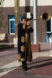 ТАШКЕНТ УЗБЕКИСТАН - 9-ое декабря 2011: Люди музыканта в традиционных kaftans играя karnay Стоковые Фотографии RF