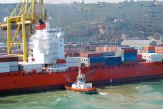 Тащите контейнеровоз нажатый шлюпкой в положение для того чтобы offload в Барселоне Испании Стоковое фото RF