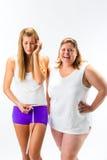 Талия тонкой и тучной женщины измеряя с лентой Стоковое Фото