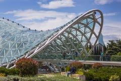 ТБИЛИСИ, GEORGIA - 7-ОЕ МАЯ: Мост мира в форме смычк p Стоковые Фотографии RF