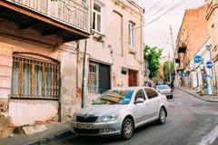 Тбилиси Georgia Припаркованный серебристый автомобиль Skoda Octavia около затрапезного здания на узкой гористой улице Стоковое Изображение