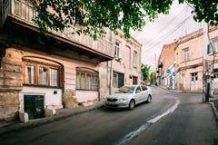 Тбилиси Georgia Припаркованный серебристый автомобиль Skoda Octavia около затрапезного здания на узкой гористой улице Стоковые Фотографии RF